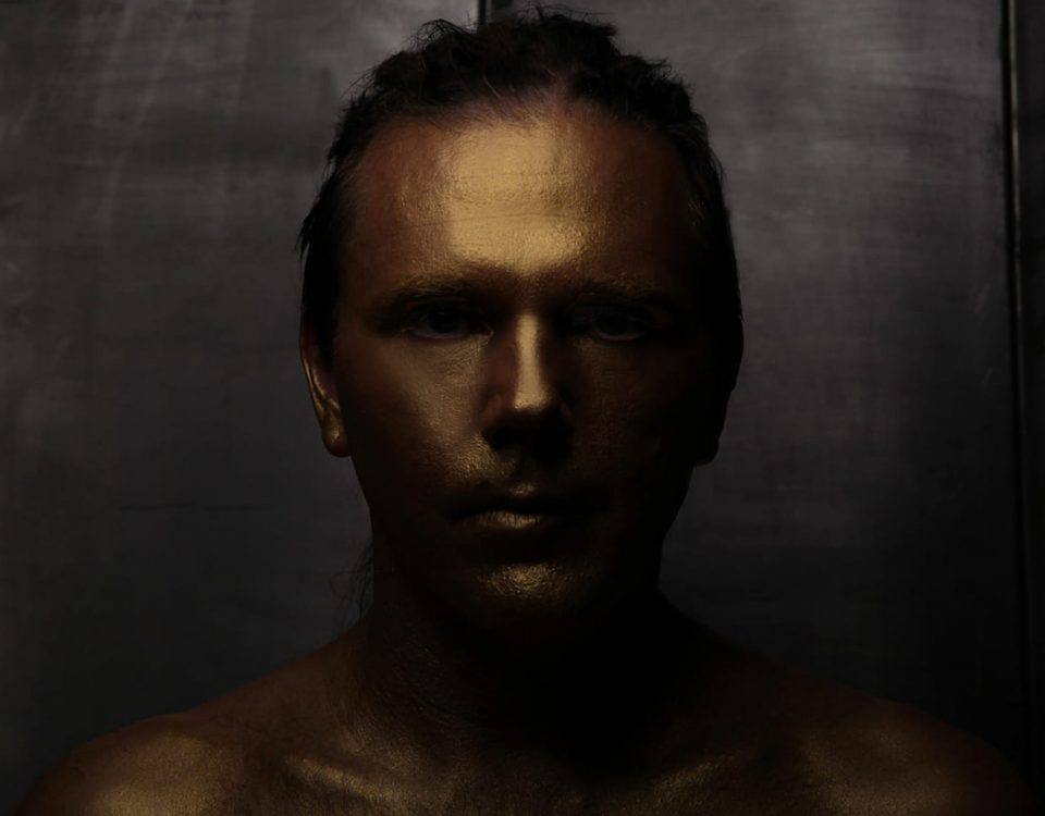 A portrait of a man in gold, the photo is dark. it is part of Shalev Man's golden project