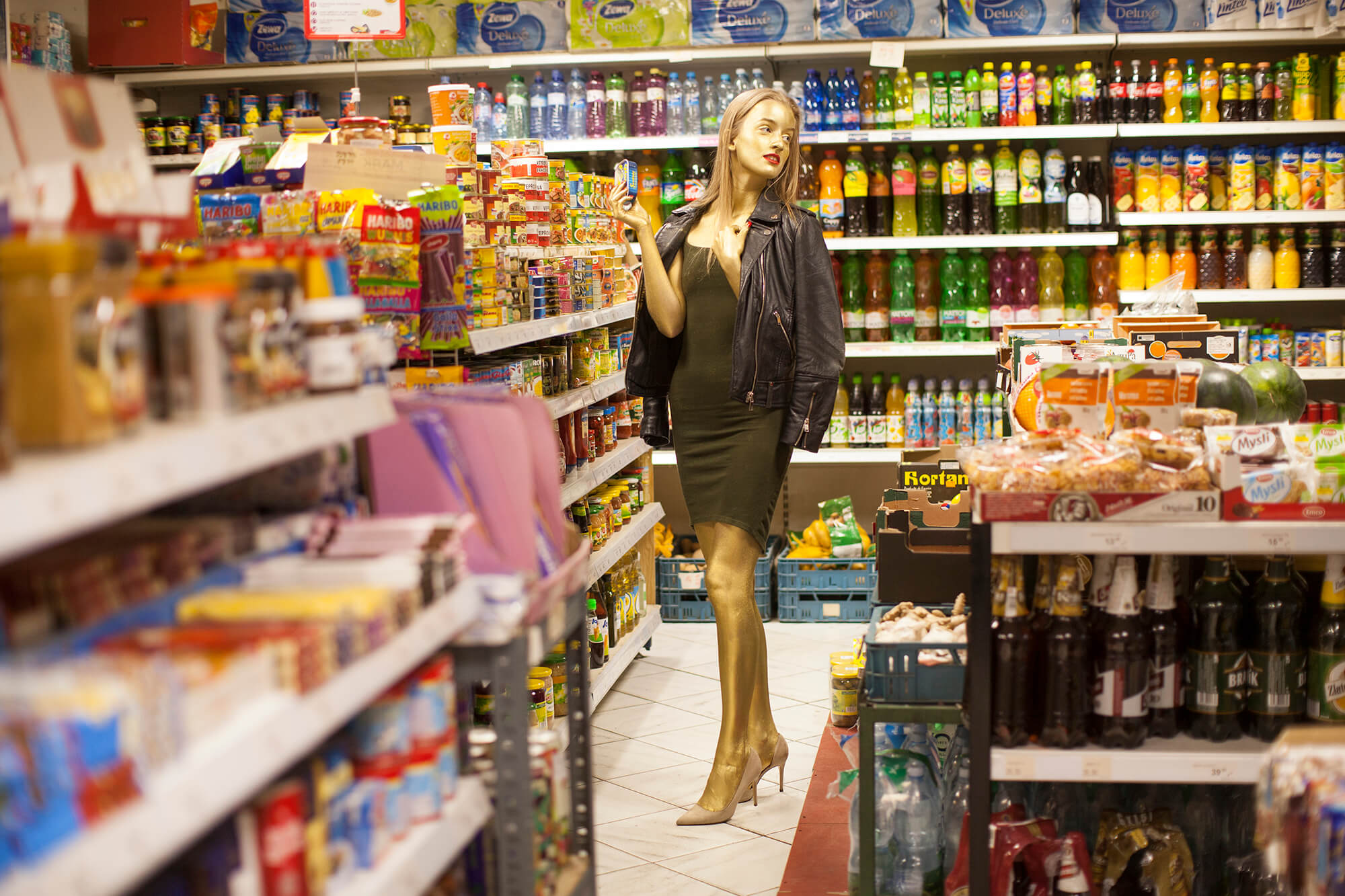A girl, covered with gold makeup, wearing a green dress, standing in a grocery