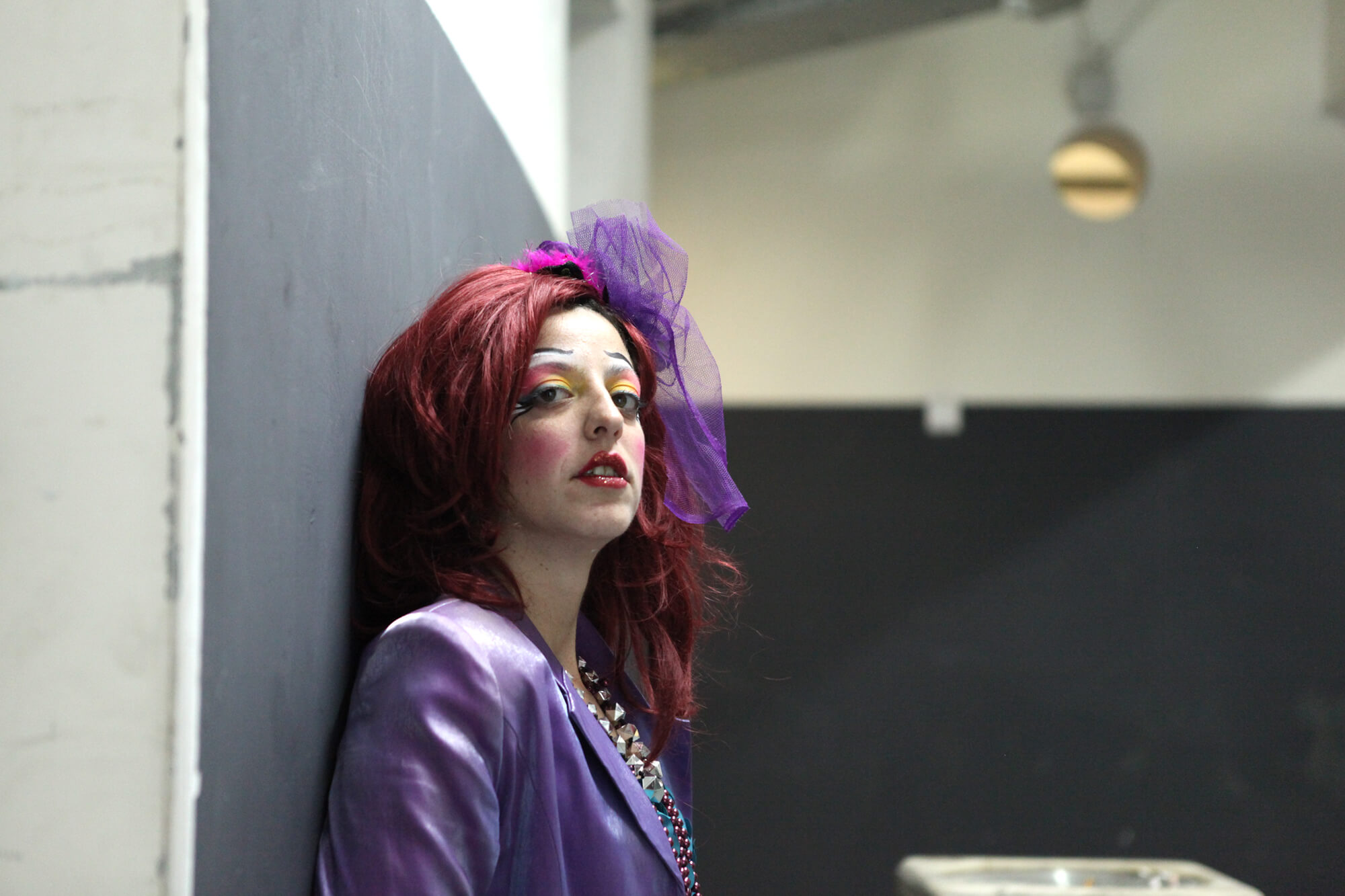 A comic actress with an orange wig and purple jacket