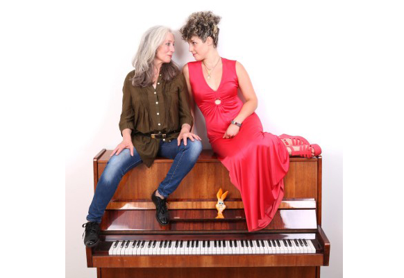 The singer Mika Sade with the poet Tzruya Laha sitting on a piano , הזמרת מיקה שדה וצרויה להב
