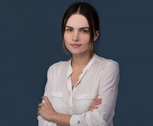 A corporate professional photo by Shalev Man. in the photo a woman with white shirt, crossed hands with a professional look