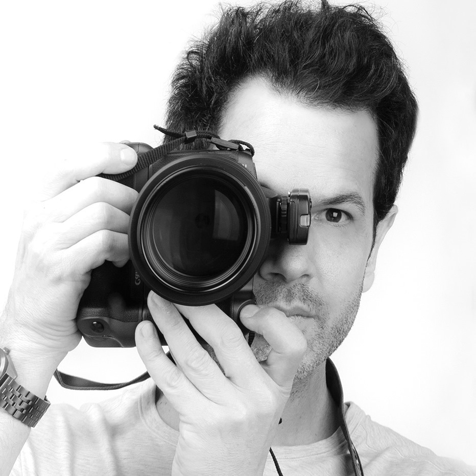 The portrait photographer Shalev in a self portrait with a camera and lens