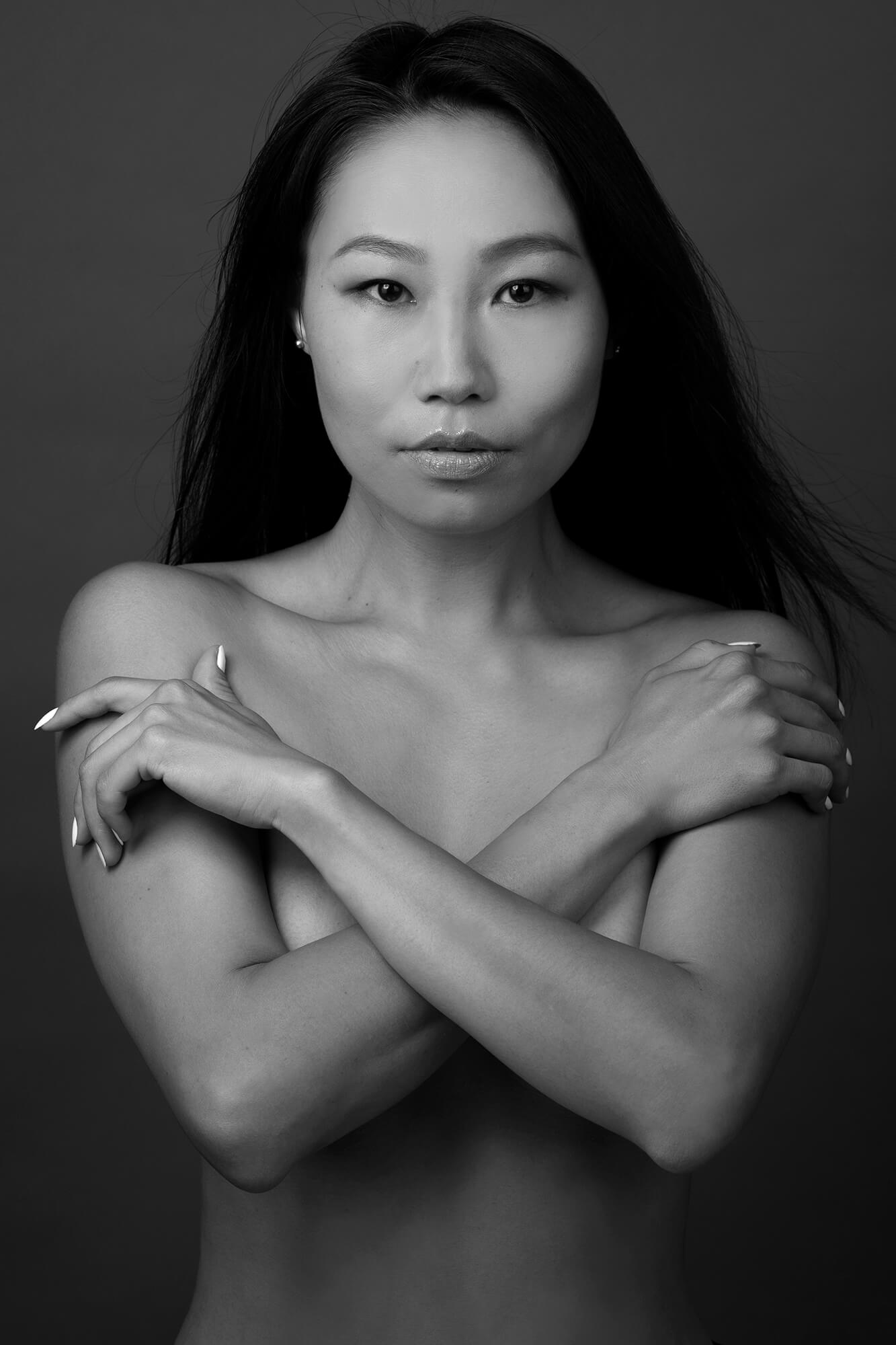 A portrait of an Asian girl on a black and white photo, standing topless and looking straight. Has a long black hair.Topless, looking straight and covering her self