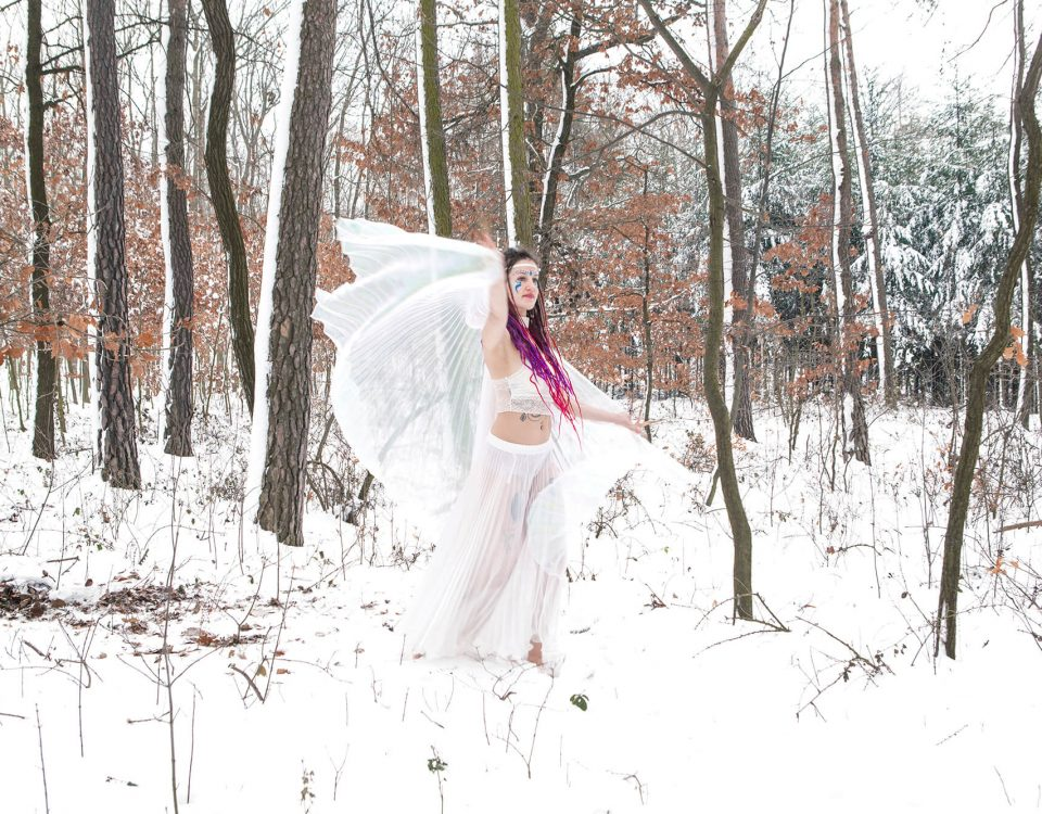 A wintar fairy dancing in the snow, a photo a woman dressed in white as a fairy, dancing in the snow
